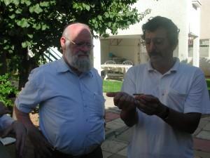 הרב דר לונינגר מסתכל על החגב הכשר בידי פרופסור זוהר עמר מומחה בנושא